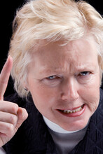 Studio Photo Of Older Woman With An Angry Look Making A Warning Finger Gesture. Black Background.