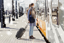 Health, Safety And Pandemic Concept - Young Woman In Protective Face Mask With Travel Bag At Empty Railway Station Over Snow