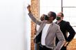 Leinwandbild Motiv Business people wearing masks brainstorming on a whiteboard, the new normal