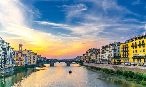 St Trinity Bridge stone bridge and boat on Arno River water and embankment promenade with buildings in historical centre of Florence city, bright blue orange evening sky clouds, Tuscany, Italy