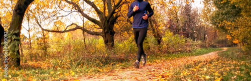 Fototapeta The young  man is running through the autumn park by pathway obraz