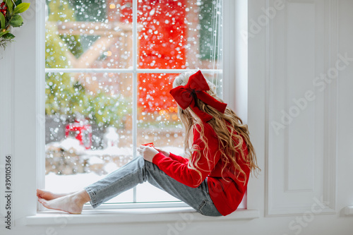 Fotomural Girl with red bow sitting on the big window with snowing background