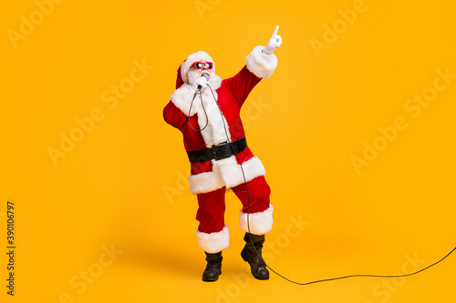 Full length photo of crazy overweight santa claus sing microphone christmas x-mas song on noel party wear headwear cap sunglass isolated over bright shine color background