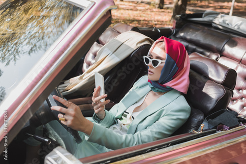 Photo Elegant woman using smartphone while driving roofless car on blurred foreground