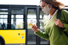 Woman With Mask Walking And Looking At Her Cell Phone At The Bus Station