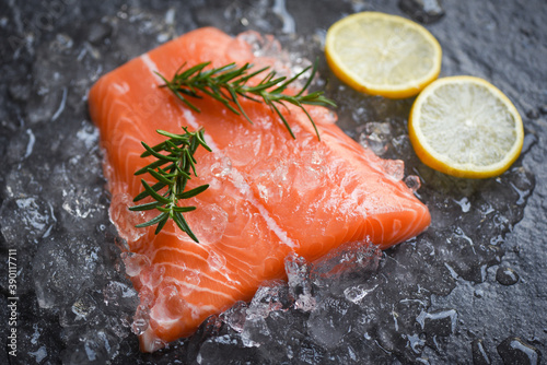 Papel de parede Fresh raw salmon fish steak on ice with rosemary food lemon and dark stone backg