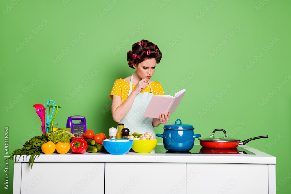 Fototapeta Photo of minded ponder girl look cook book decide what fresh organic veggie dish prepare touch chin hand wear hair rollers yellow dotted t-shirt isolated over green color background