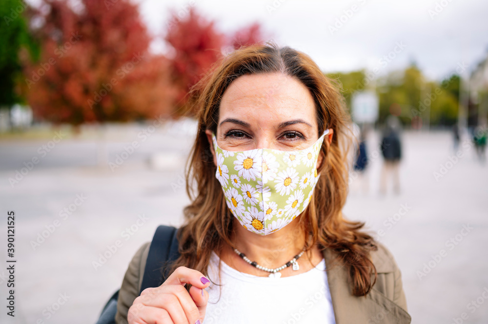 Fototapeta Woman wearing a fabric face mask in the city