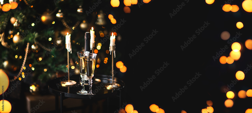 Leinwandbild Motiv - polinaloves : Two glasses and bottle of champagne standing on table with Christmas tree on a background.
