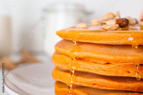 Tasty pumpkin pancakes with honey on plate, closeup