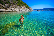 Girl With Sun Hat Relaxing And Swimming At Porto Timoni Beach At Afionas Is A Paradise Double Beach With Crystal Clear Azure Water In Corfu, Ionian Island, Greece, Europe