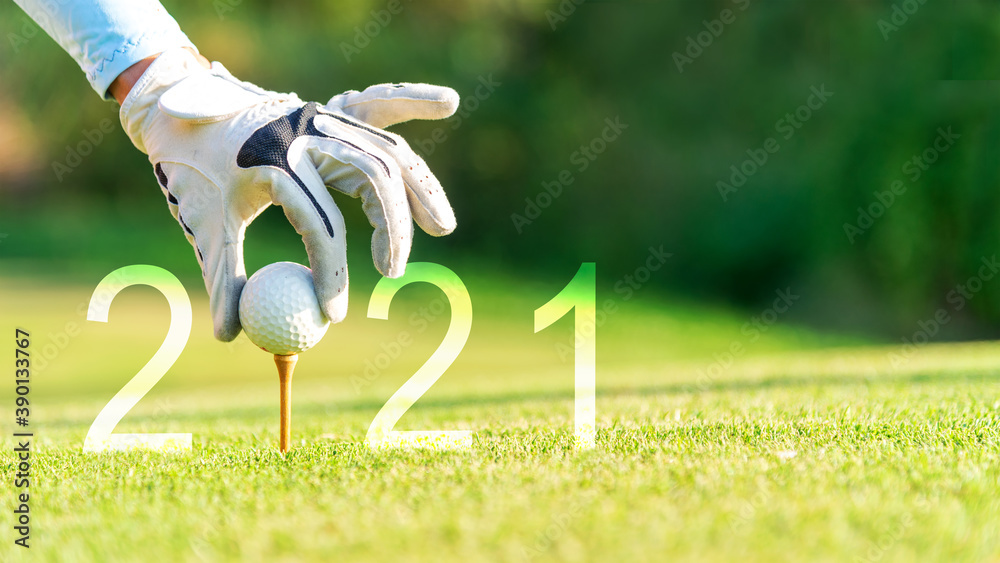 Fototapeta Golfer woman putting golf ball for Happy New Year 2021 on the green golf for new healthy.  copy space. Healthy and Holiday Concept.