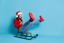 Photo Portrait Of Young Woman Riding Sled With Legs Up Isolated On Pastel Light Blue Colored Background