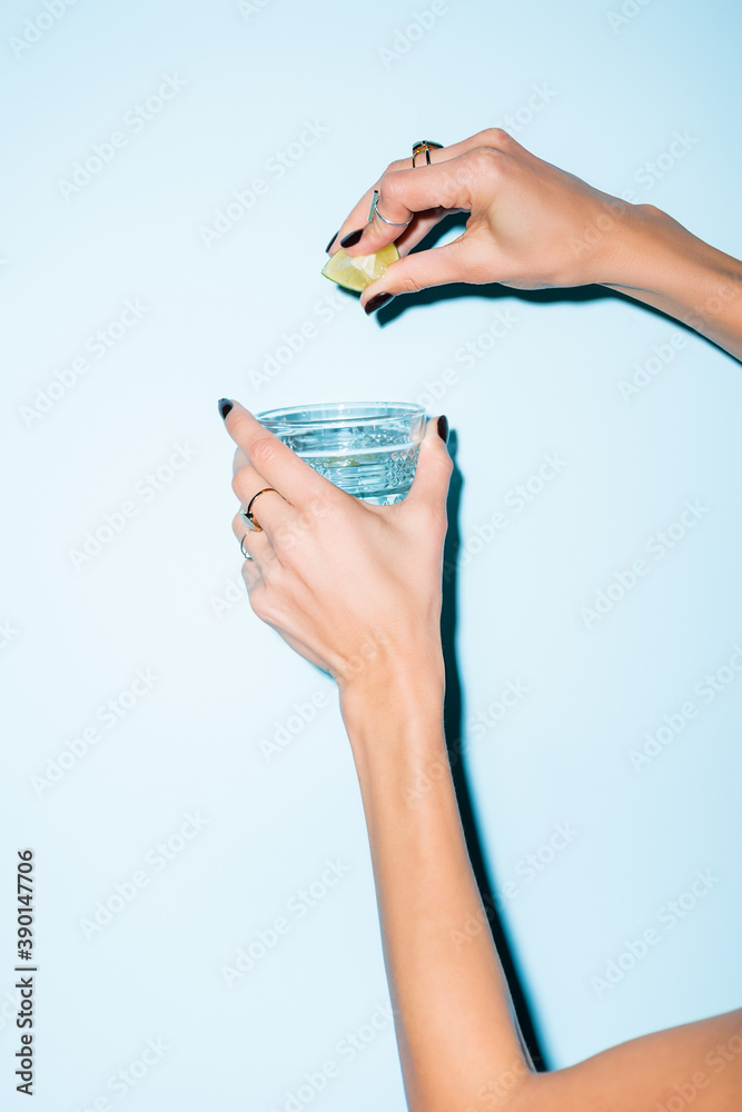 Fototapeta cropped view of woman squeezing lime in glass with alcohol drink on blue