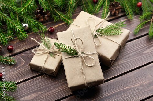 Christmas gift boxes with fir tree branches on wooden background Fotobehang