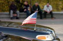Closeup Of American Flag Attached To Car. People In The Background