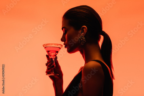 side view of young woman holding margarita cocktail with ice cubes on orange