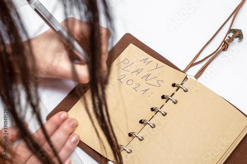 Vászonkép A brunette girl jotting down the New Year's list of goals for 2021 - a handwritten notebook describing the plan for the New Year's goals and setting goals
