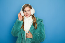 Stylish Woman In Green Faux Fur Coat And Ear Muffs Isolated On Blue