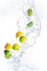 Fresh limes and lemons with water splash in midair, isolated on white background