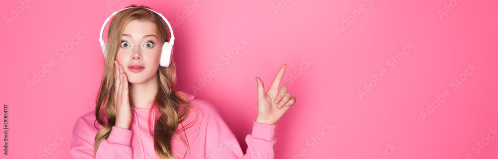 Fototapeta shocked beautiful woman listening music in headphones and pointing up on pink background, banner