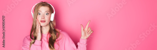 Photo shocked beautiful woman listening music in headphones and pointing up on pink ba