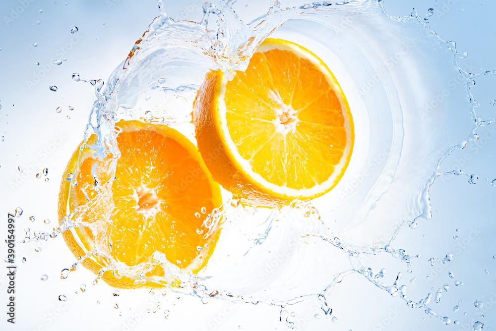 Fototapeta Two halves of orange fruit splashing into clear water.
