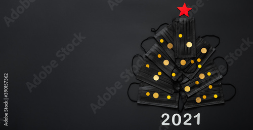 Obraz Christmas tree made from face masks and gold festive decor confetti. Face masks on black background. 2021 invitation card for New Year Eve with Copy space. Covid 19 hygiene long web banner - fototapety do salonu
