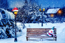 Santa Hat And New Year's Soft Toy On A Bench In The Winter Forest Against The Background Of A Village House And Lantern. Christmas Art Card. Winter Wonderland.