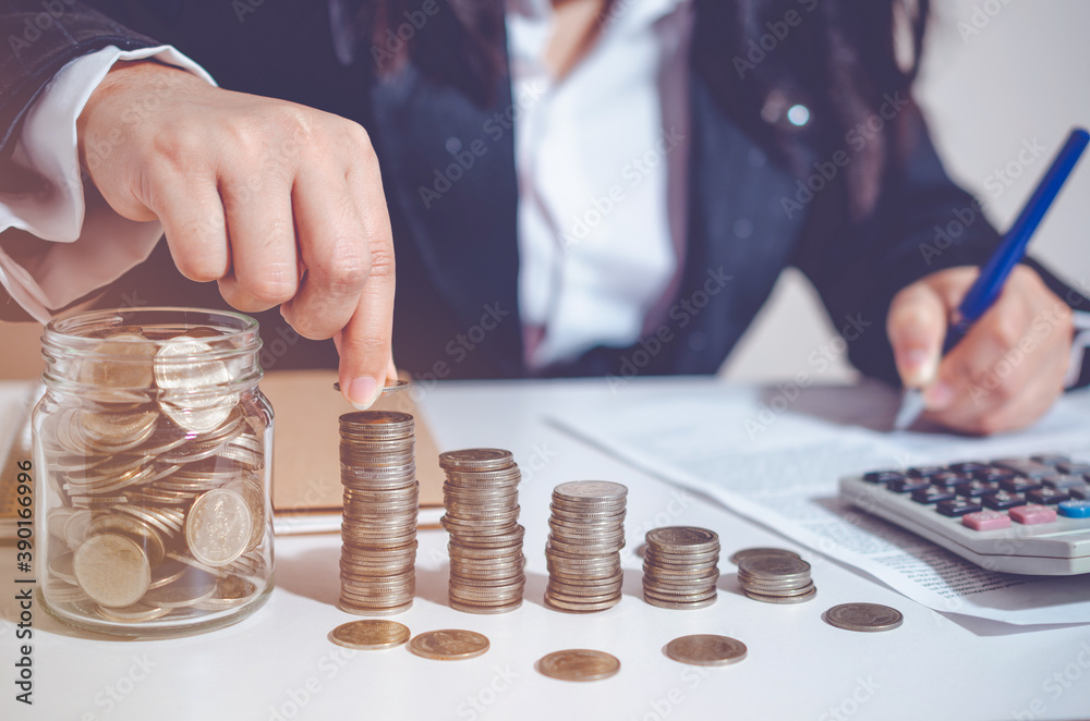 Fototapeta Closeup image businesswoman holding coins putting to stacking coins bank and calculating. concept saving money wealth for finance accounting.