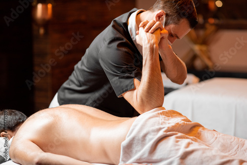 Fotomural Professional masseur in facial mask doing a deep massage to a male client at Spa salon