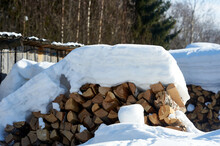Wood Piled In A Woodpile Under The Snow In Winter