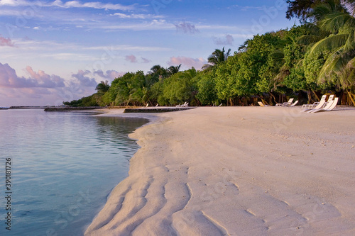 Fototapeta Sunrise on a tropical island overlooking the beach with sun loungers and tropica