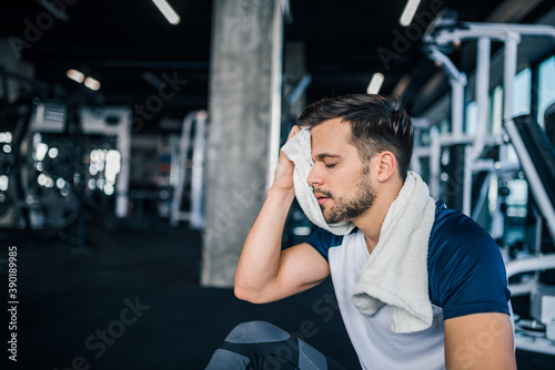 Obraz Portrait of a handsome athlete wiping sweat at the gym. - fototapety do salonu