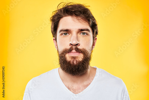 Fotografiet emotional bearded man in t-shirt cropped view yellow background studio