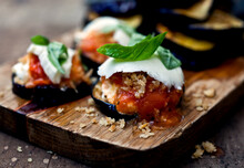 Close Up Of Eggplant Parmesan Served On Cutting Board