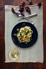 Overhead View Of Pasta With Green Puttanesca Served With Wine On Table