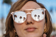 Female Face With Glasses Reflecting Sky And Palms
