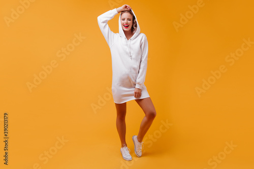 Obraz Optimistic girl puts on hood, posing for full-length photo indoors. Pretty student in white outfit smiling cute - fototapety do salonu