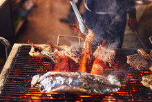Faceless Cooker Frying Crayfishes On Grill In Outdoors Market