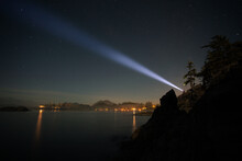 A Person Shining A Bright Flashlight Into The Night Sky Over The Ocean