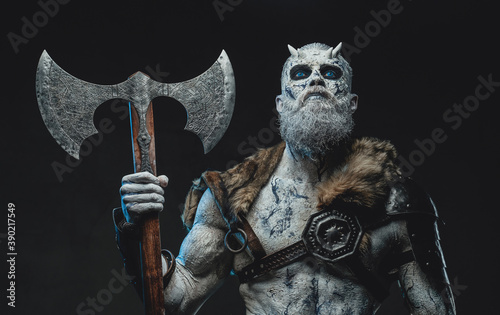 Photo Frozen dead warrior with horns and white skin in dark armour holding two handed axe in twilight