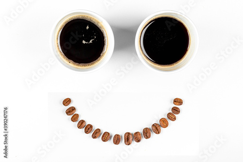 Fotografie, Obraz two cups of espresso with a smile from coffee beans on a white background