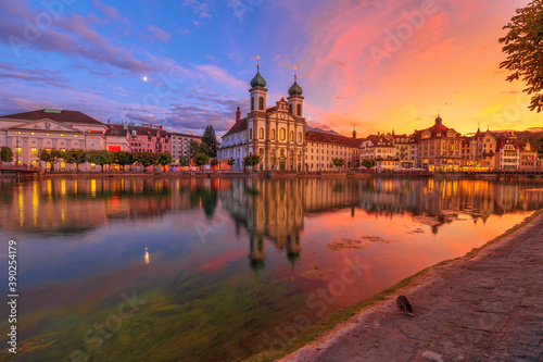 Amazing sunset with colorful clouds in city downtown of Lucerne in Central Switzerland. Jesuitenkirche or Jesuit Church of St. Francis Xavier reflecting on Reuss river of Lucerne's historical city.