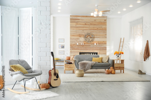 Obraz Cozy living room interior with comfortable furniture, guitar and autumn decor - fototapety do salonu