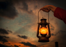 Female's Hand Holding A Lantern With The Beautiful Sunset In The Background
