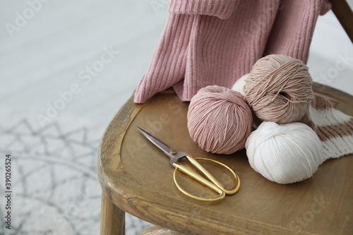 Yarn balls and scissors on wooden chair indoors, space for text Canvas Print