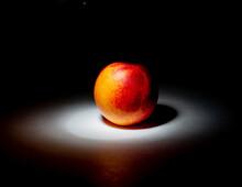 Closeup Of A Single Fresh Nectarine Under A Spotlight In A Dark Setting