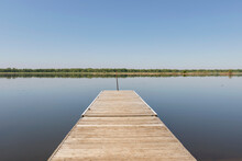 A Wood Pier Juts Over A Still Lake With A Treeline In The Background
