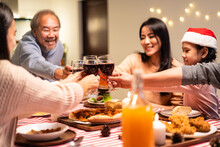 Asian Big Family Clinking Wine Glasses And Enjoying Christmas Party.